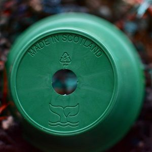 the base of a dark green ocean plastic pot showing drainage hole